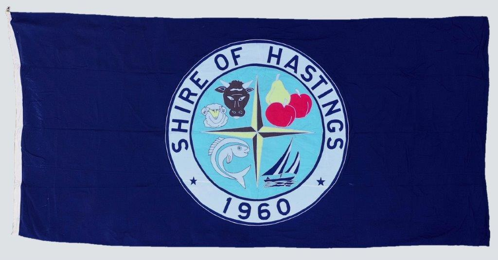 Shire of Hastings Flag. Hand - sewn fabric with embroidered stitching displaying symbols for the Shire's identity; Livestock, fruit industry, fishing and boats.