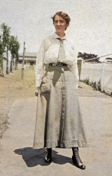 Colour photograph of a smiling Miss Ula Robinson circa 1918. She is wearing a long skirt and blouse with a tie, leather belt and lace up boots.